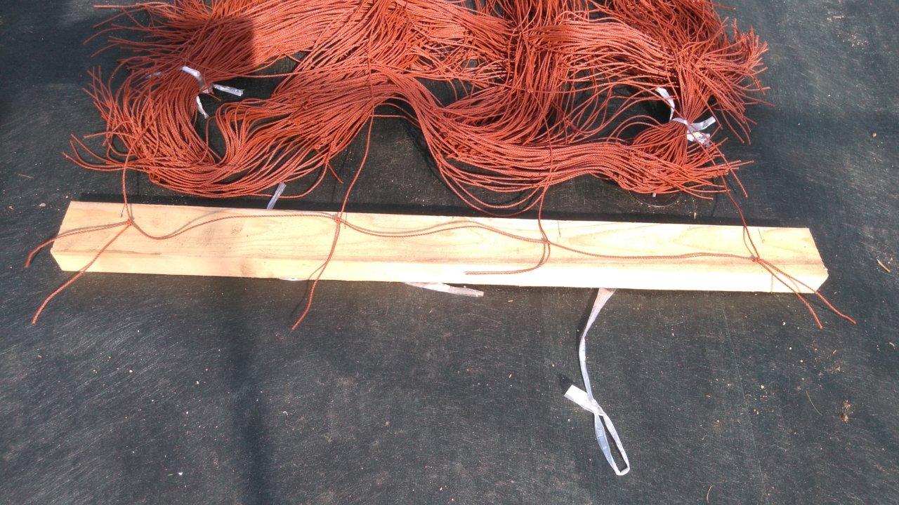 フラワーネットの端を木材に合わせてのこぎりで溝を作る